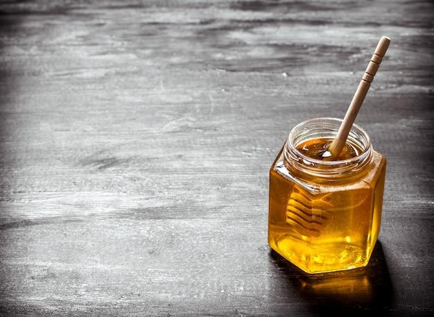 Kruik verse honing met een lepel. op zwarte rustieke achtergrond.