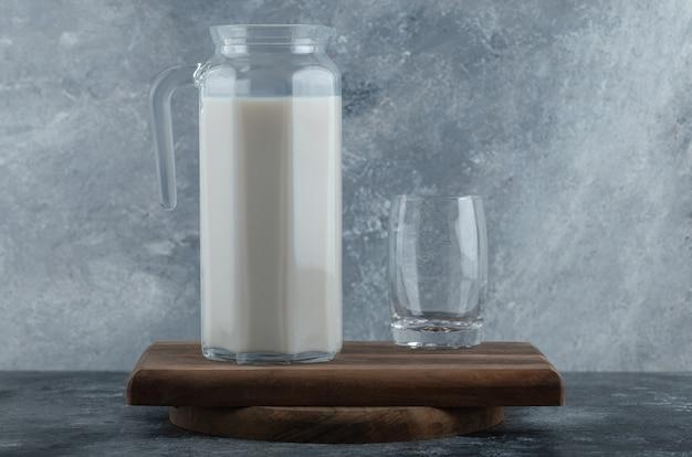 Kruik verse melk en glas water op een houten bord.