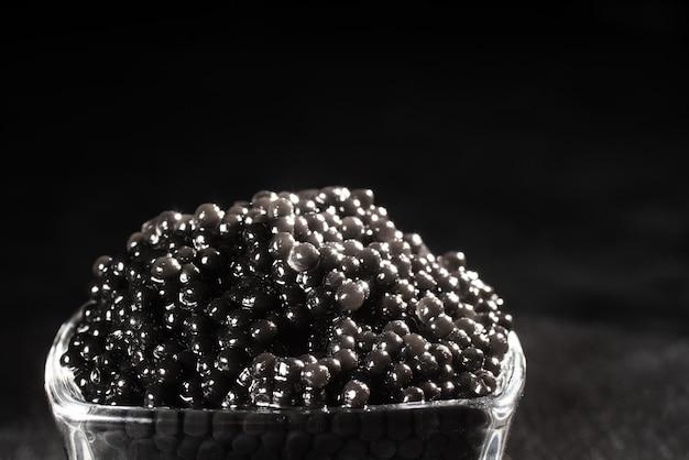 Kruik zwarte kaviaar op donkere ruimte
