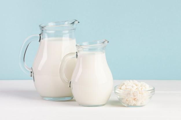 Kruiken met melk op blauwe achtergrond worden gevuld die