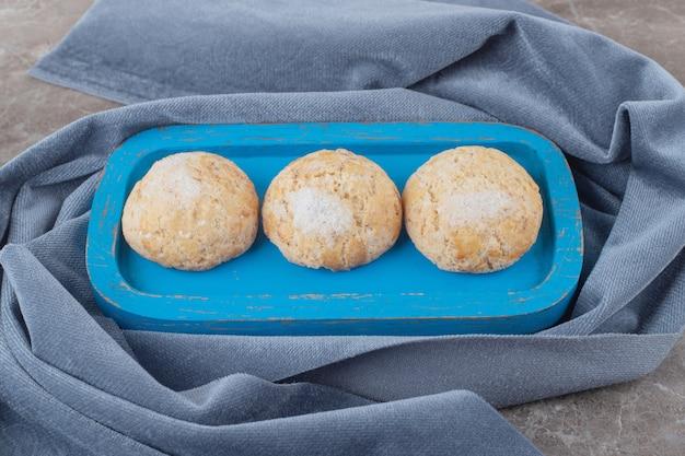 Kruimelige koekjes op een blauwe schaal op een stuk stof op marmer