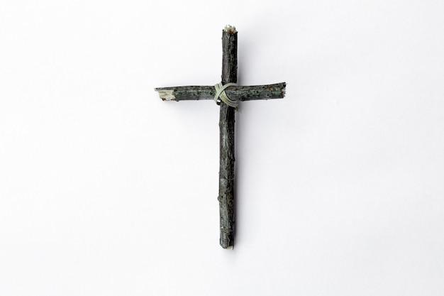 Kruis dat van boomtak wordt gemaakt die op witte achtergrond wordt geïsoleerd