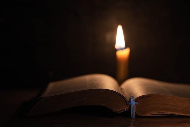 Kruis met bijbel en kaars op een oude eiken houten tafel.
