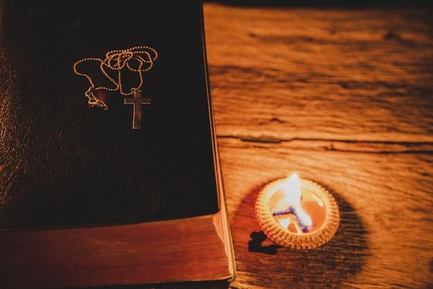 Kruis met de heilige bijbel en kaars op een oude eikenhouten tafel.
