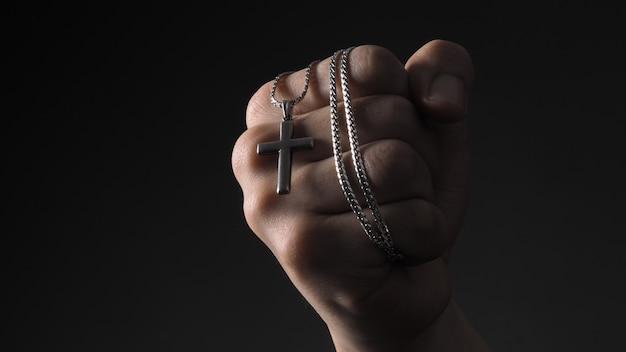 Kruis of kruisbeeld hanger en ketting in man hand.