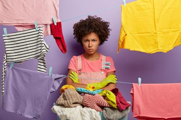 Kruis ongelukkige huisvrouw staat met gevouwen armen, handen gewassen wasgoed, boos op veel taken over huis, gebruikt wasknijpers, geïsoleerd over violette muur. mensen, huishoudelijk werk en wasconcept.