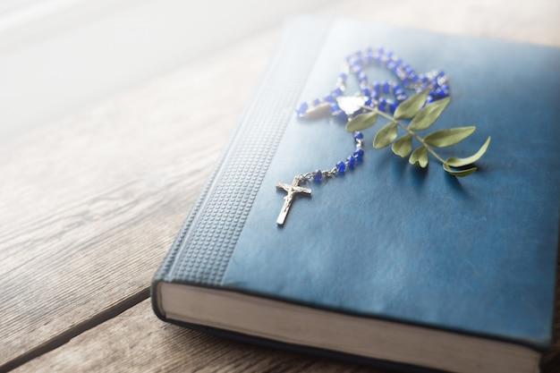 Kruis op de antieke bijbel op een houten tafel. holy bo