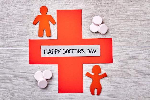 Kruis, pillen en felicitatiekaart. het vieren van professionele medische dag.