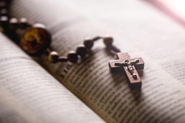 Kruisbeeld op bijbel in vlekfocus en exemplaarruimte, concept van geloof