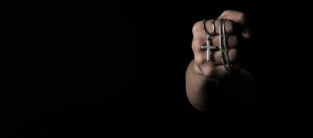 Kruisbeeldhanger of kruisteken gemaakt van zilver en in de hand van de man houden staat voor bidden voor iemand