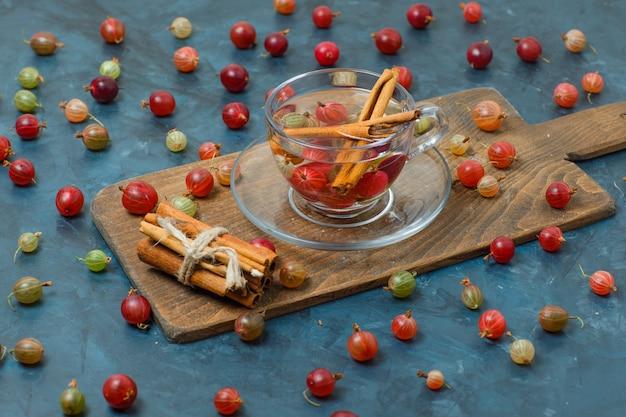 Kruisbessen met drankje, specerijen hoge hoek uitzicht op donkerblauw en snijplank