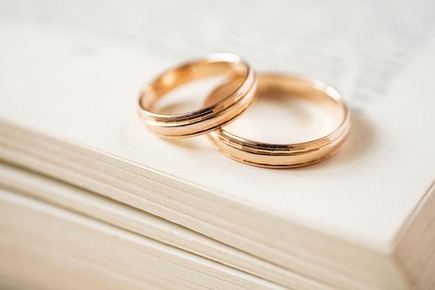 Kruisende gouden trouwringen liggen aan de rand van een open boek. bovenaanzicht.