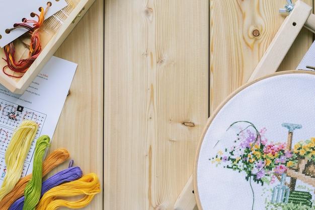Kruissteken set: borduurring met geborduurd bloemenpatroon, canvas, kleurrijke draden, kleurenpalet. houten tafel. hobby, handgemaakt interieurconcept. diy. kopieer ruimte