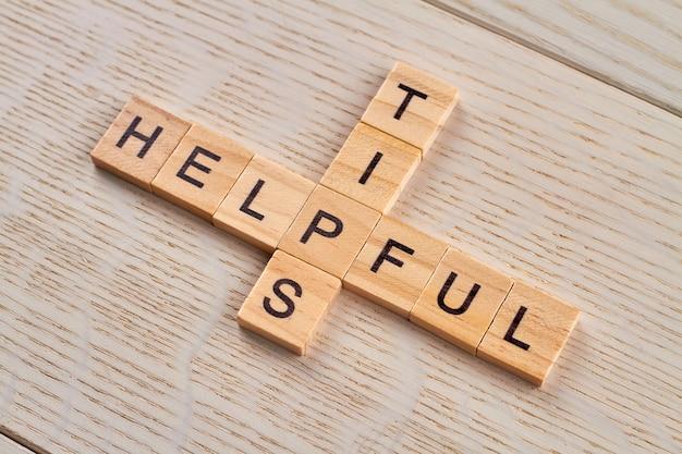 Kruiswoordpuzzel met woorden handige tips. houten tegels met hoofdletters op een houten bord.