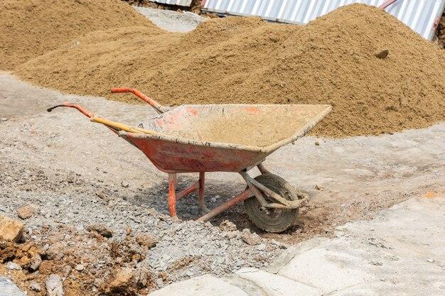 Kruiwagen in de bouwwerf met zand op een grond