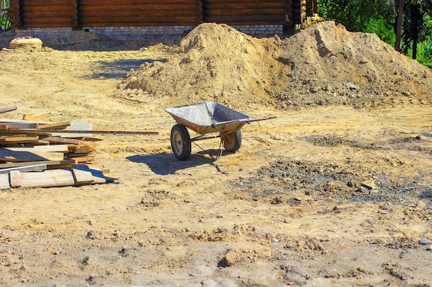 Kruiwagen op de werf tussen het zand en planken
