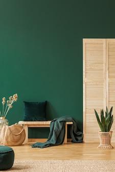 Kruk met deken en kussen in groen woonkamerinterieur met plant en rotan tas. echte foto