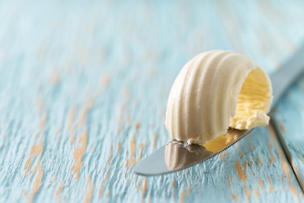 Krul van boter op een mes op een blauwe houten tafel, met kopie ruimte.