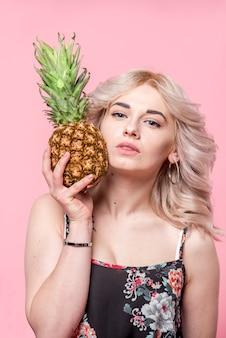 Krullend aantrekkelijke vrouw met ananas in de hand