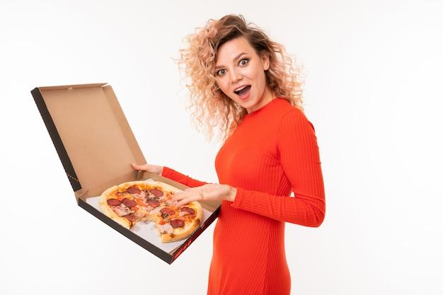 Krullend blond meisje in een rode jurk houdt een doos pizza op een witte achtergrond