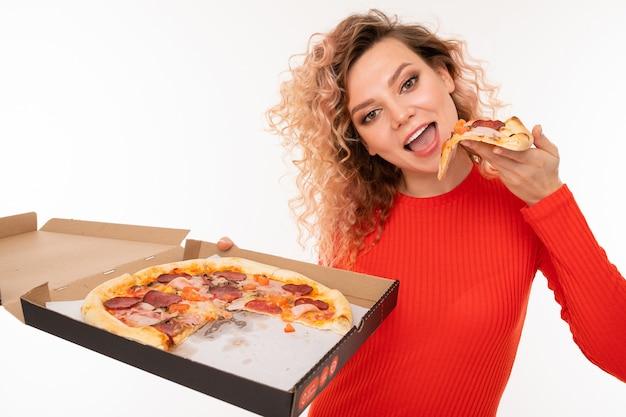 Krullend blond meisje probeert een stuk pizza met een doos in haar hand op wit