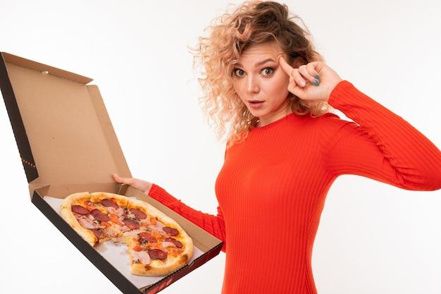 Krullend blond meisje toont denken met een pizzadoos in haar hand op wit