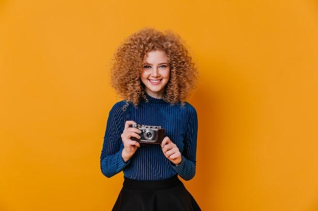 Krullend blonde dame in strakke blauwe trui glimlacht en houdt retro camera op gele ruimte.