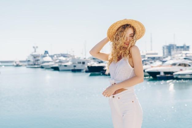Krullend blondje met een hoed haalt verrast koket haar schouders op tegen de achtergrond van schepen en de zee. kalme zee