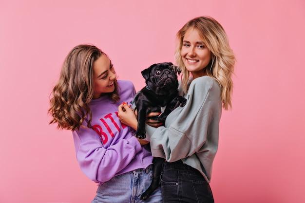 Krullend brunette dame in trendy kleding bulldog pup kijken en lachen. spectaculaire blanke meisjes die vrije tijd doorbrengen met hun hond.