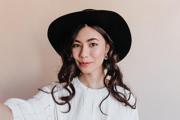 Krullend chinese vrouw selfie te nemen. vooraanzicht van aziatisch model in hoed poseren op beige achtergrond.