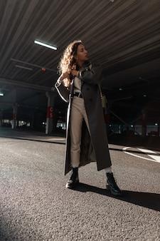 Krullend fashion model meisje in stijlvolle vintage lange jas, trui, broek, laarzen en tas loopt op straat. stedelijke vrouwelijke stijl en schoonheid. zonlicht en schaduwen