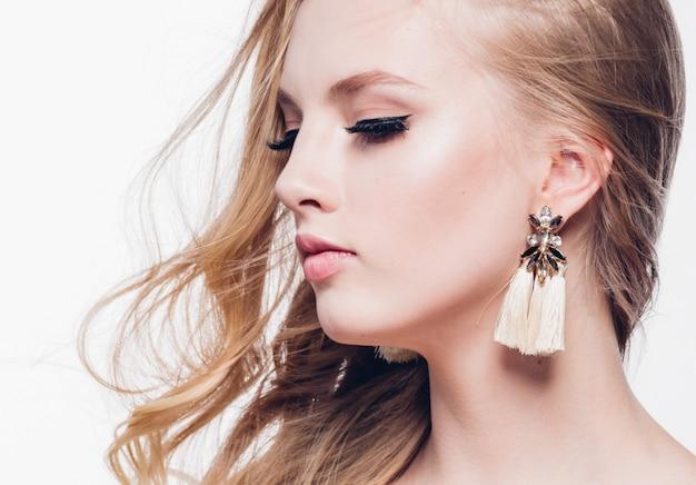 Krullend haar blonde vrouw met lang mooi kapsel en schoonheid wimpers geïsoleerd op wit. studio opname.