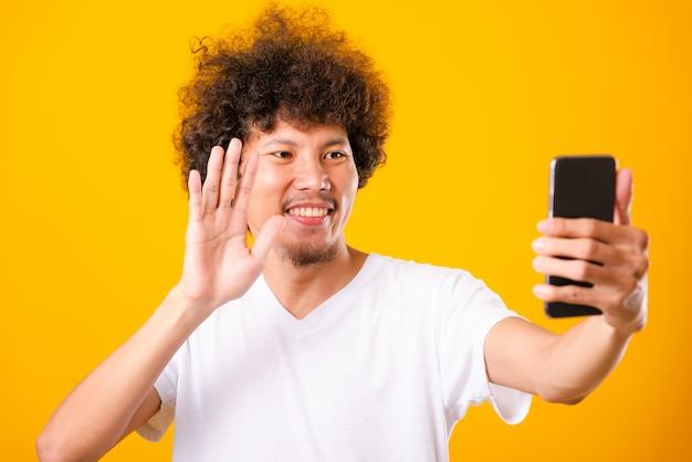 Krullend haar die van de portret het aziatische knappe mens selfie met smartphone nemen