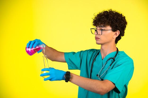 Krullend haarjongen in medisch uniform en handmaskers die chemische reactie op geel doen.
