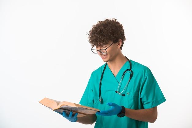 Krullend haarjongen in medisch uniform en handmaskers die een oud boek lezen en glimlachen.
