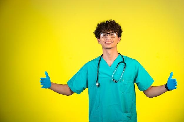 Krullend haarjongen in medisch uniform en handmaskers met omhoog duimen.