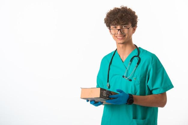 Krullend haarjongen in medisch uniform met een groot boek in beide handen.