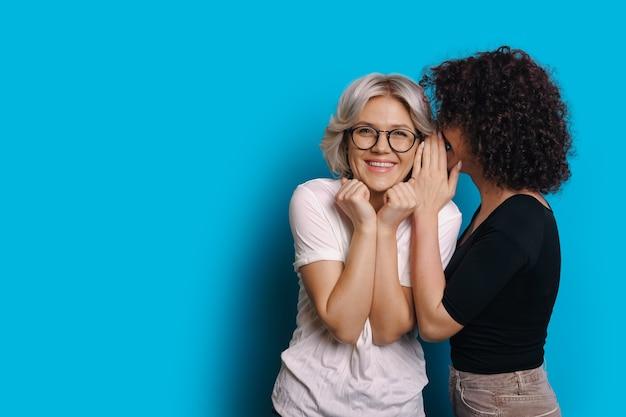Krullend haired kaukasisch meisje praat iets geheim met haar blonde vriend die een bril draagt en op een blauwe lege ruimteachtergrond poseert