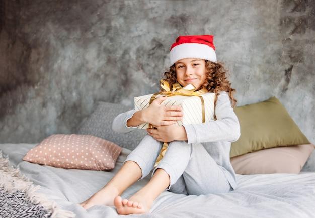 Krullend haired mooi tween-meisje in kerstmanhoed en pyjama's die op bed met grote giftdoos zitten, de tijd van de kerstmisochtend