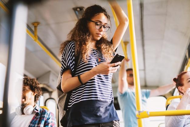 Krullend jong studentenmeisje die voor een bar in openbaar vervoer houden en aan de muziek via haar telefoon luisteren.