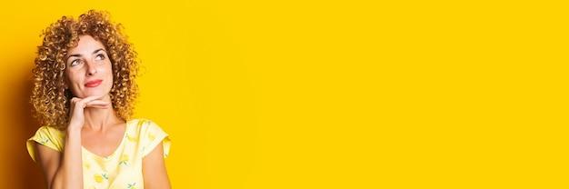 Krullend jonge vrouw houdt haar hand onder haar kin kijkt bedachtzaam naar boven op een gele achtergrond