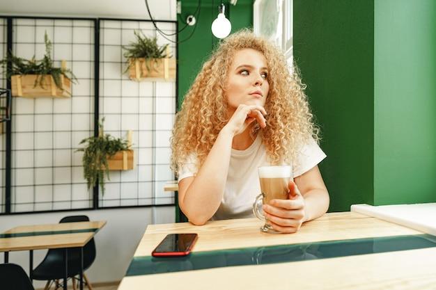 Krullend jonge vrouw zitten aan de tafel in de coffeeshop en ontspannen met een kopje koffie