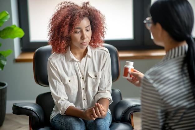 Krullend jongedame in gesprek met haar psychotherapeut