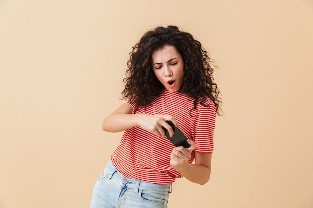 Krullend jongedame spelen door mobiele telefoon.