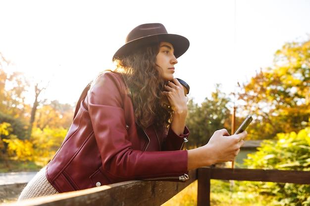 Krullend jongedame wandelen in de herfst park koffie drinken met behulp van mobiele telefoon.
