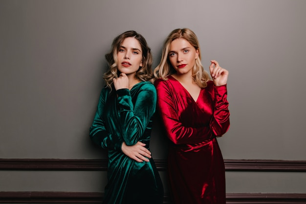 Krullend kaukasisch model in groene kleding. binnenportret van twee volwassen zussen in fluwelen outfits.
