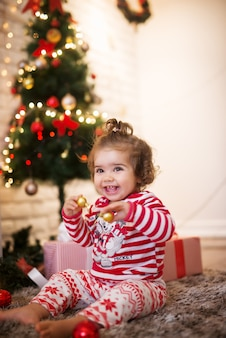 Krullend klein kind vrouw met paardenstaart spelen met ornamenten zittend op een tapijt voor kerstvakantie.