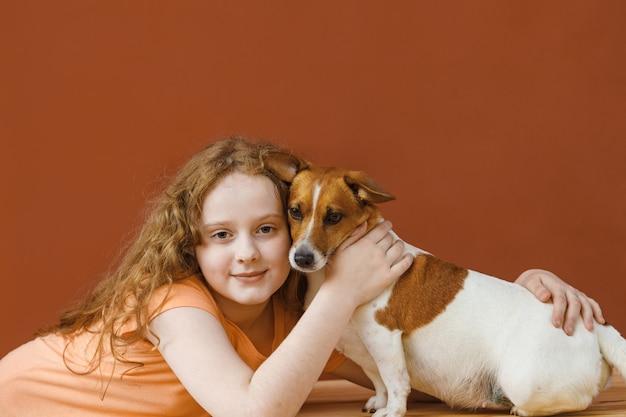 Krullend meisje dat haar vriendenhond omhelst.