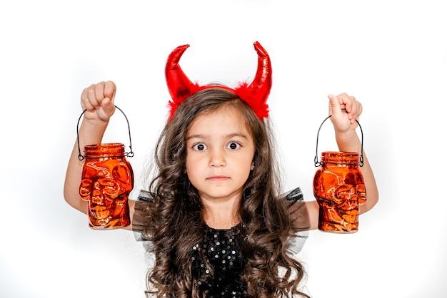 Krullend meisje in een heksenkostuum met schedellantaarns op een witte studioachtergrond copyspace