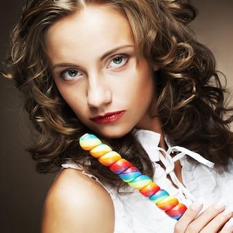 Krullend meisje met een lolly in haar hand
